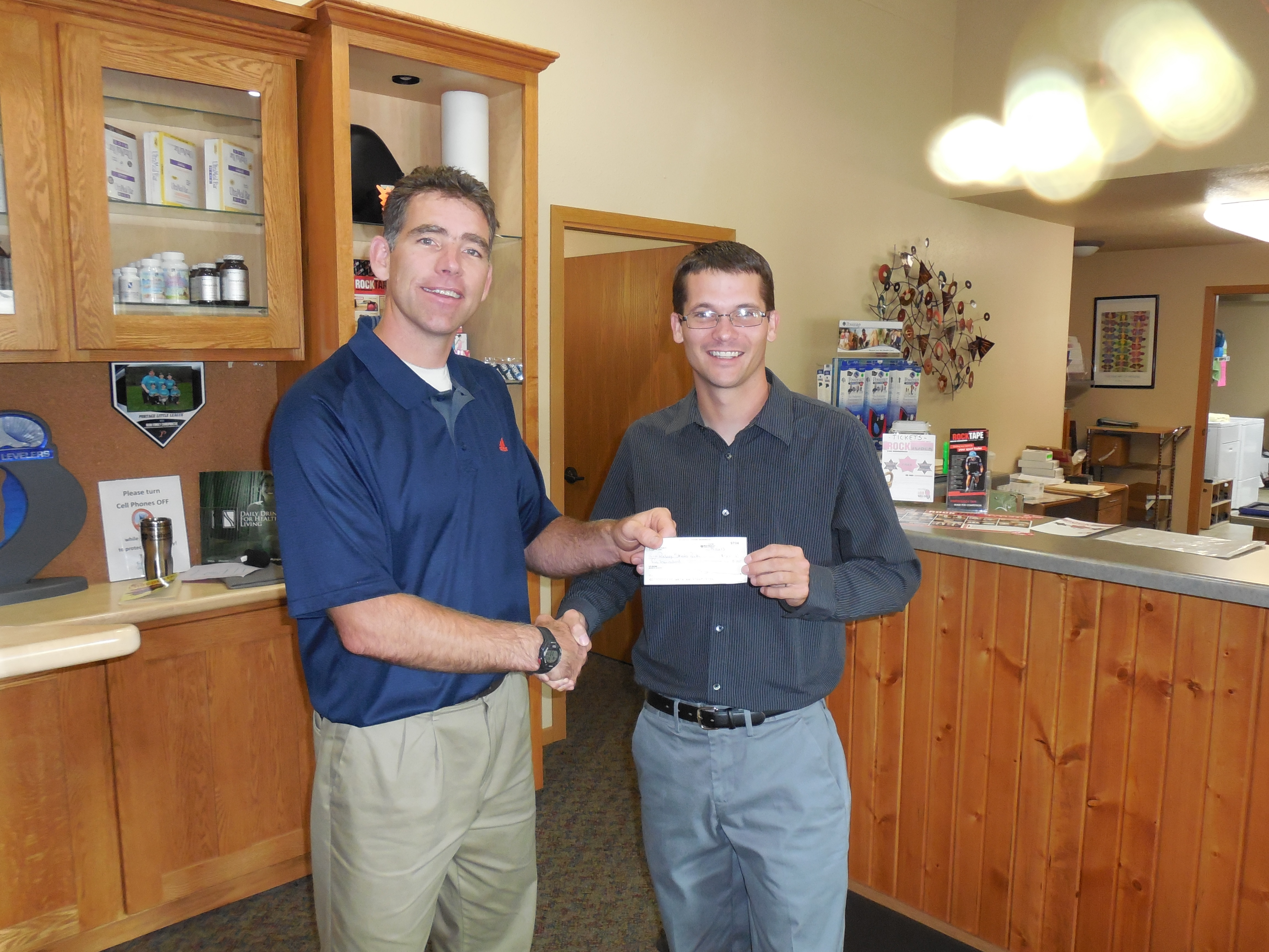 Dr. Kevin Blau presents a check to President Kyle Little.